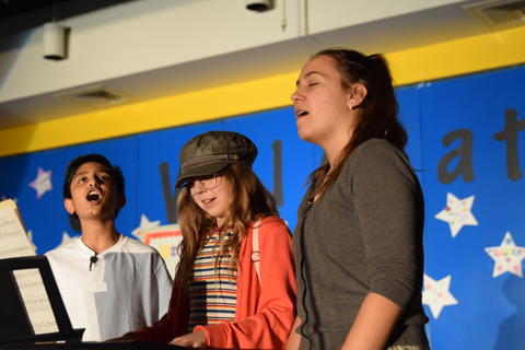 three young performers onstage singing