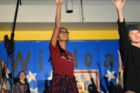 young girl onstage gesturing with one arm raised