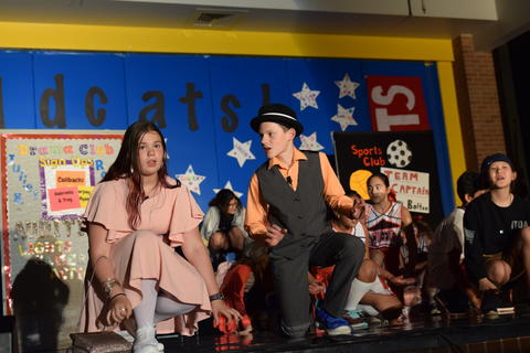 young boy and girl onstage in conversation