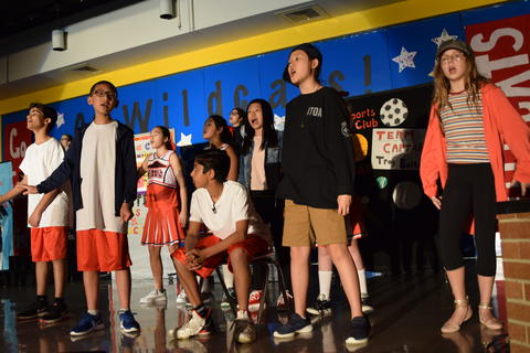 young performers onstage singing and dancing
