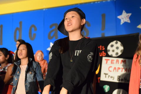 young girl wearing side-angled ball cap onstage in conversation