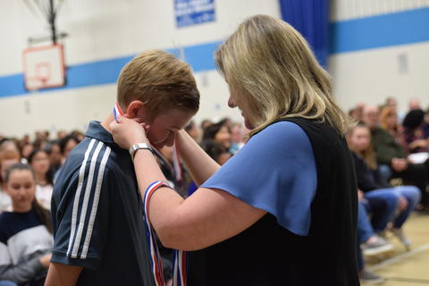 Boy receiving recognition medal from adult