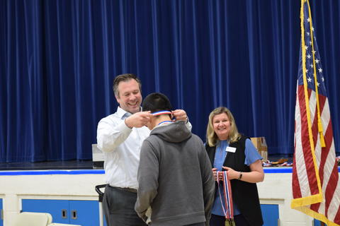 middle school boy receiving recognition medal from adult man