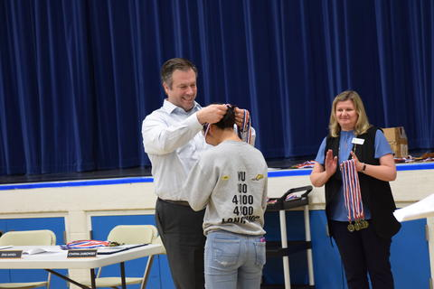 middle school boy receiving recognition medal from man