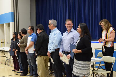 adults holding recognition certificates