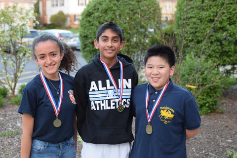 three children with medals posing outdoors for student recognition photo