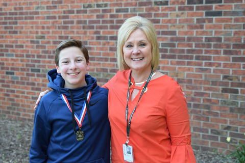 boy with medal and adult woman posing for student recognition photo