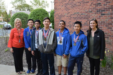 women and middle school boys posing for student recognition photo