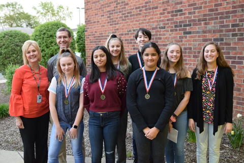 adults and girls posing outdoors for student recognition photo