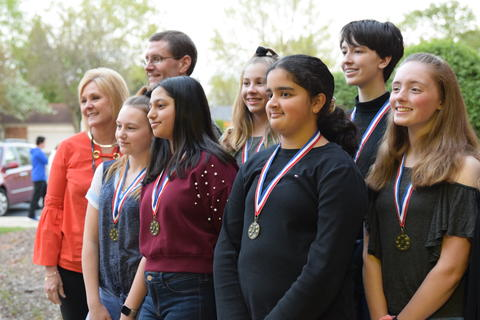 adults and students posing for student recognition photo