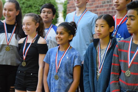 smiling students wearing recognition medals posing for photo
