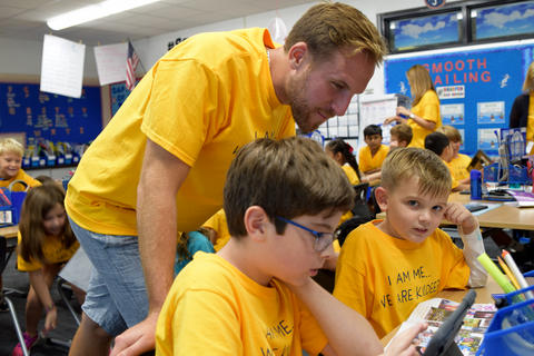 Young male teacher looks over shoulder of two elementary boys, all wearing yellow school T-shirts