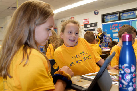 two smiling girls, wearing yellow school T-shirts, looking at iPad screen together