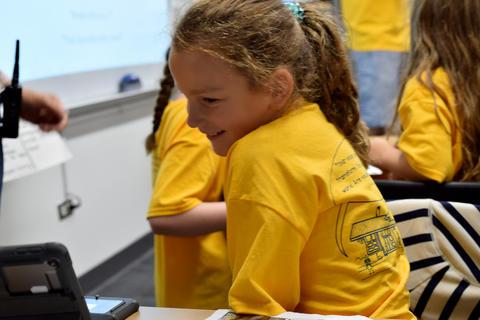 Smiling young girl in profile, wearing yellow school T-shirt