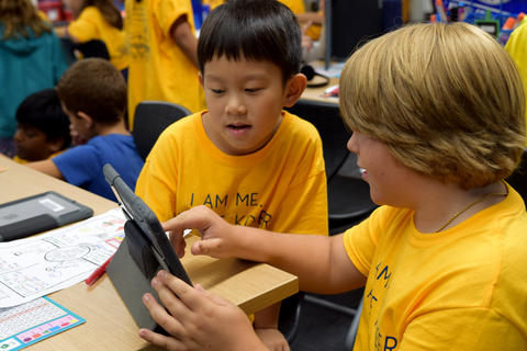 Two young boys, both wearing yellow school T-shirts, looking at iPad screen