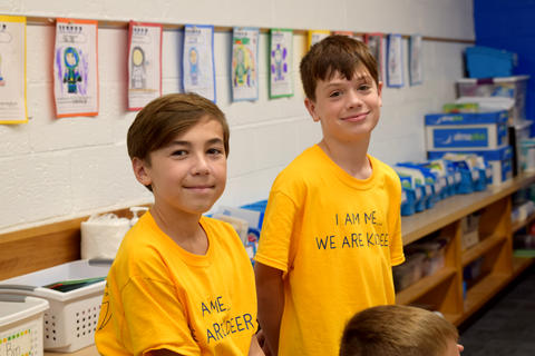 Two smiling young boys, both wearing yellow school T-shirts, posing for camera