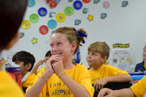 Smiling young girl wearing yellow school T-shirt, with hands clasped and held to her chin