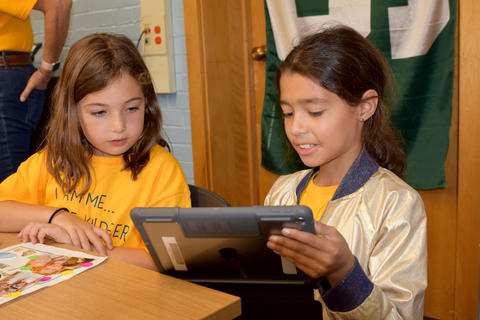 two young girls, seated side by side, looking at iPad screen together