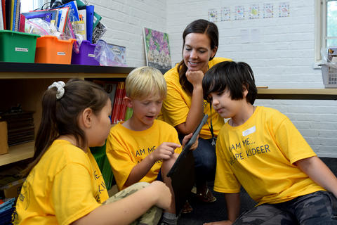 Smiling teacher and three young students, all wearing yellow school T-shirts, looking at iPad