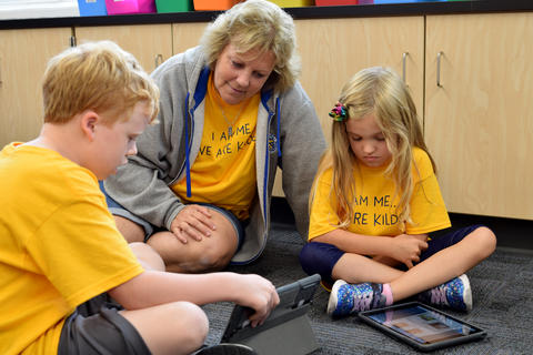 Teacher seated on floor between young girl and boy students, all wearing yellow school T-shirts, looking at iPad screen