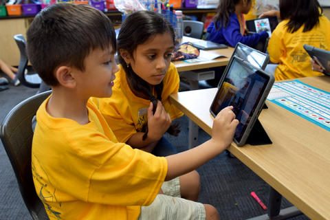 young boy and girl, wearing yellow school T-shirts, studying monitor screen