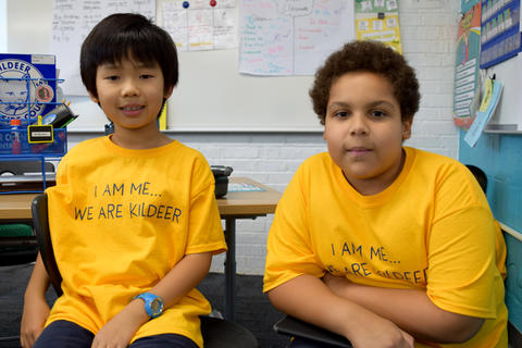 two smiling young boys wearing yellow school T-shirts, posing for camera