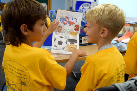 two smiling young boys in matching yellow school T-shirts, talking