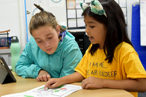 two young girls, side-by-side, looking at a paper together