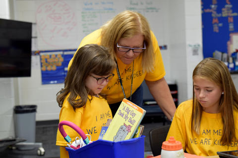Teacher and two young girls, all wearing yellow school T-shirts, looking at book