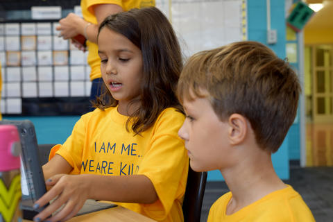 Young girl and boy, wearing yellow school T-shirts, looking at iPad screen together