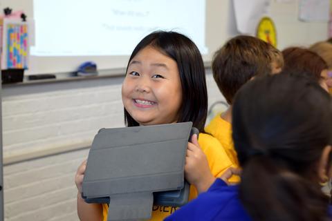 Smiling girl posing for camera, holding iPad