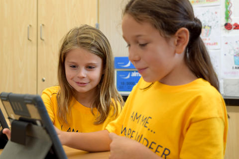 Two smiling young girls, wearing yellow school T-shirts, looking at iPad screen
