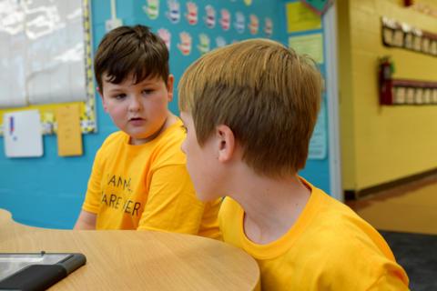 Two young boys, wearing yellow school T-shirts, talking