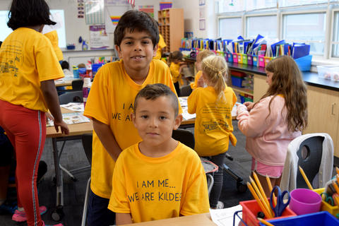 Seated young boy and older boy standing behind, both wearing yellow school T-shirts