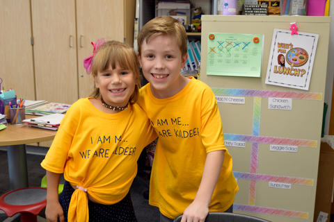 smiling boy and girl, standing with arm around each other, both wearing yellow school T-shirts