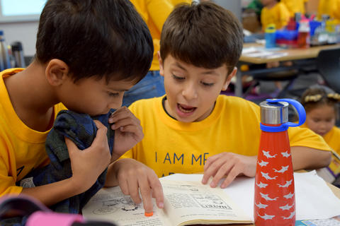 two young boys talking and studying book, both wearing yellow school T-shirts