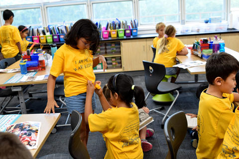 Kneeling young girl tying fashion knot on classmate's yellow school T-shirt matching one she is wearing