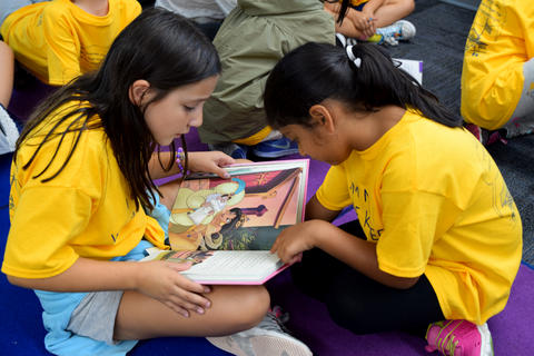 two young girls seated cross legged on floor facing one another and studying book, both wearing yellow school T-shirts
