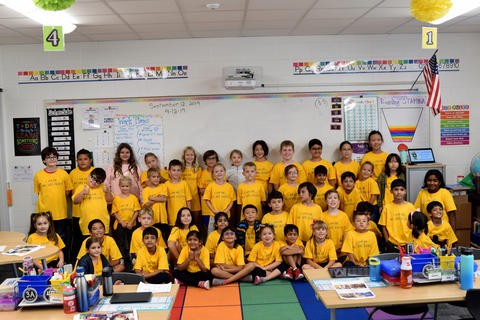 Class picture of students in 3 rows, wearing yellow school T-shirts