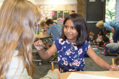 young girl talking with classmate