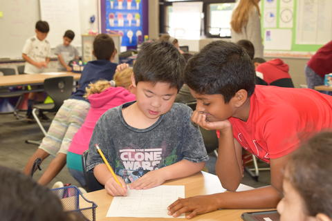 two young boys talking and completing list together