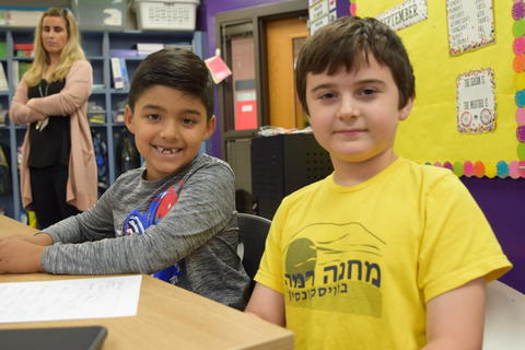 two young boys in classroom smiling at camera