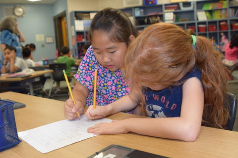 two young girls completing list together