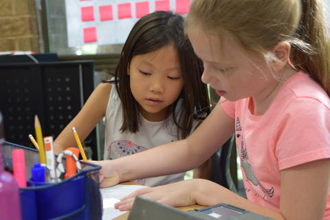 two young girls talking and completing list together