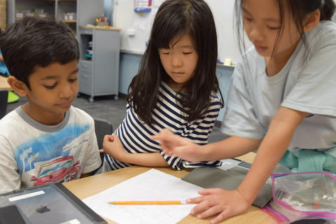 Young boy and two girls talking and completing list together