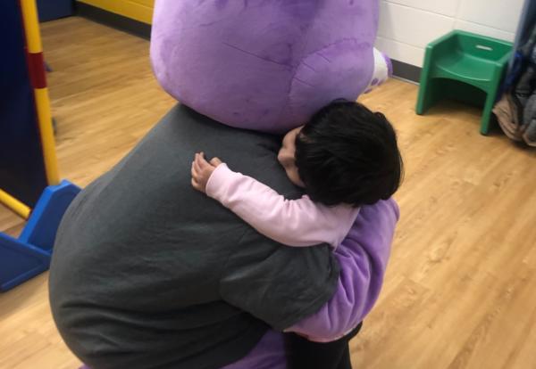 Child hugging big purple bear