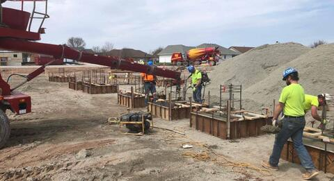 The team is working hard pouring and finishing the concrete column pads at the south wall of the courtyard.