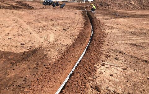 With the light pole bases installed, conduit is being trenched from pole to pole.  At completion, these conduits will be buried about two feet below the surface.
