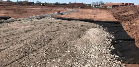 The fabric and stone is being installed on the large east parking lot.  By the end of next week, this area will be able to be used for construction staging.