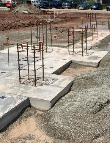 Concrete column pads and footings for Area B are being poured. These foundations will support the south wall of the library facing the existing school.